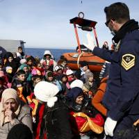 A Greek coast guardsman talks to refugees and migrants sitting on the deck of the Ayios Efstratios Coast Guard vessel following a rescue operation at open sea between the Turkish coast and the Greek island of Lesbos on Monday. | REUTERS