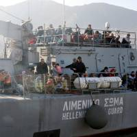Migrants and refugees arrive aboard a Hellenic coast guard ship at the port of Lesbos island on Monday. | AFP-JIJI