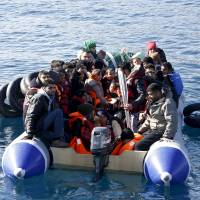 Refugees and migrants are seen on a dinghy as they approach a Greek coast guard vessel during a rescue operation at open sea between the Turkish coast and the Greek island of Lesbos on Monday. | REUTERS