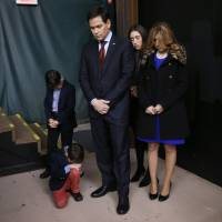 Republican presidential candidate Sen. Marco Rubio and his family pray during the opening of a caucus site Monday in Clive, Iowa. | AP