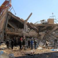 People gather around the rubble of a hospital supported by Doctors Without Borders (MSF) near Maaret al-Numan, in Syria's northern province of Idlib, on Monday after the building was hit by suspected Russian airstrikes. MSF confirmed in a statement that a hospital supported by the aid group in Idlib province was 'destroyed in air strikes.' | GHAITH OMRAN / AL-MAARRA TODAY / AFP-JIJI