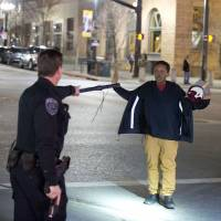 A police officer stops a boy as he walks away from a crowd that formed after an officer-involved shooting in Salt Lake City on Saturday. Unrest broke out in a neighborhood after what appears to be a shooting involving a police officer. | AP