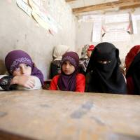 Girls attend a class at their school in a village outside Yemen's capital Sanaa Tuesday. | REUTERS