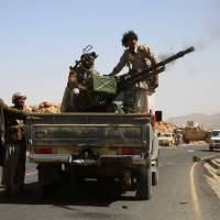 Yemeni tribesmen from the Popular Resistance Committees, supporting forces loyal to Yemen's Saudi-backed President Abed Rabbo Mansour Hadi, fire a heavy machine-gun as they hold a position in the Nehm region, west of Marib city, on Tuesday. | AFP-JIJI