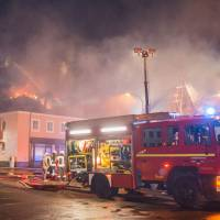 A fire engine stands in front of a burning building in Bautzen, eastern Germany, Sunday. The fire damaged a former hotel that was being converted into a refugee home and two people were detained after hindering firefighters' work, police said Sunday, days after an incident in which a mob blocked a bus carrying asylum-seekers in the same state. | RICO LOEB / DPA VIA AP