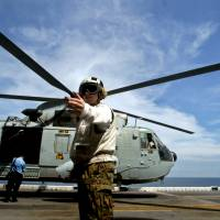 U.S. Marines Corps personnel guide the media on board the USS Boxer LHD as a helicopter prepares for takeoff at a location off Goa, India, in October 2006. | REUTERS