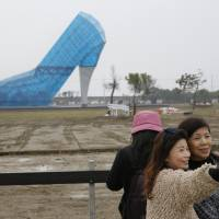 Vsitors take a selfie Jan. 28 in front of a giant glass structure shaped like a high-heel shoe being built as a wedding hall in southern Chiayi, Taiwan. | AP