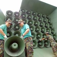 South Korean soldiers work on a battery of loudspeakers along the border with North Korea in Paju in June 2004. | AFP-JIJI