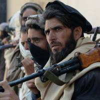 Afghan alleged former Taliban fighters carry their weapons before handing them over as part of a government peace and reconciliation process at a ceremony in Jalalabad on Wednesday. | AFP-JIJI