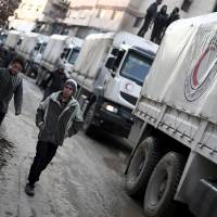 A Red Crescent convoy carrying humanitarian aid arrives in Kafr Batna, in the rebel-held Eastern Ghouta area on the outskirts of Damascus, on Tuesday during an operation in cooperation with the U.N. to deliver aid to thousands of besieged Syrians. | AFP-JIJI