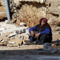A women rests near rubble on the ground in the town of Darat Izza, province of Aleppo, Syria, Sunday. | REUTERS