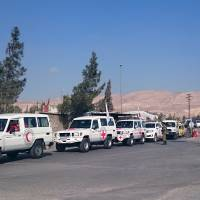 A humanitarian aid convoy consisting of the Red Cross and Syrian Arab Red Crescent wait to deliver aid at the entrance of the insurgent-held town of Mouadamiya, southwest of Damascus, Feb. 3. | REUTERS