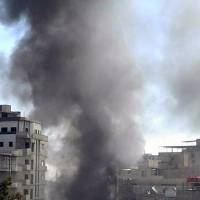 In this photo released by the Syrian official news agency SANA, smoke rises after three bombs exploded in Sayyda Zeinab, a predominantly Shiite Muslim suburb of Damascus, on Sunday. | SANA VIA AP