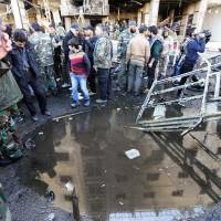 Syrian pro-government forces and residents gather at the site of suicide bombings in the area of a revered Shiite shrine in the town of Sayyida Zeinab, on the outskirts of the capital Damascus, on Sunday. | AFP-JIJI