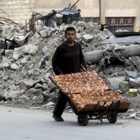 A man selling pastries walks past the rubble of damaged buildings in the rebel held al-Shaar neighborhood of Aleppo, Syria, on Feb. 10, 2016. | REUTERS