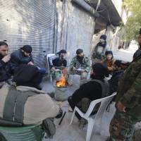 Rebel fighters of al-Jabha al-Shamiya (Levant Front) warm themselves around a fire near the justice palace in the old city of Aleppo, Syria, Jan. 28. | REUTERS