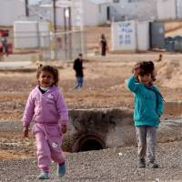 Young Syrian refugees stand at the Azraq refugee camp in northern Jordan on Saturday. | AFP-JIJI