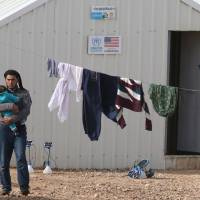 A Syrian refugee man carrying a baby stands at the Azraq refugee camp in northern Jordan on Saturday. | AFP-JIJI