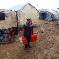 An internally displaced Syrian girl carries water cans at a refugee camp near the Bab al-Salam crossing, opposite the Turkey's Kilis province, on the outskirts of the northern border town of Azaz, Saturday. | REUTERS