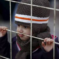 A Syrian boy looks through a gate at the Oncupinar border crossing in the southeastern Turkish city of Kilis on Thursday. | REUTERS