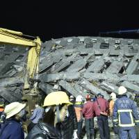 Rescue personnel work at the site of a collapsed building in the southern Taiwanese city of Tainan following a strong magnitude-6.4 earthquake on Feb. 6. | AFP-JIJI