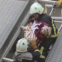 A child is rescued from a toppled building after a 6.4-magnitude earthquake struck Tainan, Taiwan, on Saturday. | AP