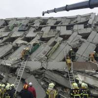 Rescue personnel work at the site where a 17-story apartment building collapsed during an earthquake in Tainan, southern Taiwan, on Saturday. | REUTERS