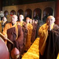Monks pray for the dead and survivors of a powerful earthquake that hit Tainan, southern Taiwan, last week, at Beijing's Guangji Temple on Friday. | REUTERS