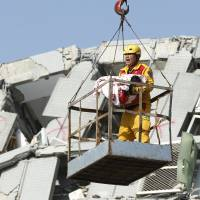 An emergency worker carries a rescued 6-month-old girl from the rubble of a collapsed building in Tainan, Taiwan, Sunday. Rescuers on Sunday found signs of life within the remains of a high-rise residential building that collapsed in a powerful, shallow earthquake in southern Taiwan that killed over a dozen people and injured hundreds. | AP