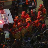 Rescue workers carry 28-year-old Vietnamese woman identified as Chen Mei-jih, rescued from the rubble of a collapsed building complex, to a waiting ambulance in Tainan, Taiwan, Monday. More than 100 people are believed to still be under the debris in a powerful quake that struck on Saturday. | AP
