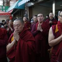 Tibetan monks pray for the missing people said to be still inside the collapsed building complex in Tainan, Taiwan, Sunday. | AP
