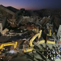 As night falls, emergency rescue workers continue to search the rubble of a collapsed building complex in Tainan, Taiwan, Monday. | AP