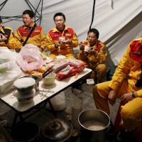 Rescue workers have a reunion dinner Sunday on the eve of the Chinese New Year, near a 17-story apartment building that collapsed after an earthquake hit Tainan, southern Taiwan. | REUTERS
