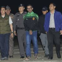 Thai police escort Artur Segarra Princep, 36, of Spain after arriving by helicopter on Monday at the police airport in Bangkok from Cambodia. He is the prime suspect in the gruesome murder of a fellow Spaniard. | AP