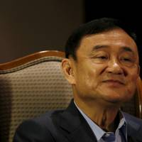 Former Thai Prime Minister Thaksin Shinawatra speaks an interview in Singapore on Tuesday. | REUTERS
