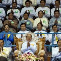 Myanmar President Thein Sein (behind flowers) is seen in a June 2013 file image. The military ruler advocated a slow pace of reforms, although critics say that left corruption unchallenged. | AFP-JIJI