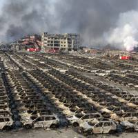 Smoke billows from the site of an explosion that reduced a parking lot filled with new cars to charred remains at a warehouse in Tianjin, China, on Aug. 13. | AP