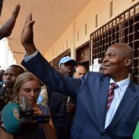Faustin Archange Touadera leaves a polling station in Bangui on Feb. 14 after casting his ballot for delayed legislative elections and a presidential runoff vote in the Central African Republic. | AFP-JIJI