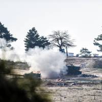 Tanks of the Turkish army shoot in the direction of Syria, near the Syrian border some kilometres from the Oncupinar crossing gate in Kilis, south central Turkey, on Monday. The Turkish army struck positions of Kurdish fighters inside Syria for a second day in response to incoming fire, state media said, as an explosive standoff between Ankara and Syrian Kurds intensified. | AFP-JIJI
