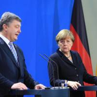 Angela Merkel, Germany's chancellor, looks on as Petro Poroshenko, Ukraine's president, speaks during a news conference at the Chancellery in Berlin on Monday. | BLOOMBERG