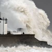 Waves crash over the seawall at Porthcawl in Wales, Mondayas winds of nearly 100 mph battered Britain after Storm Imogen slammed into the south coast bringing fierce gusts and torrential downpours. | JOE GIDDENS / PA VIA AP