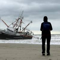 A woman watches the boat Carolina Queen III at Rockaway, New York, Thursday. High seas and strong winds stranded the 76-foot commercial fishing vessel off New York's Rockaway Beach and capsized a U.S. Coast Guard boat that rushed to help on Thursday, but no one was injured, a Coast Guard spokeswoman said. | REUTERS