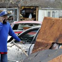 Timothy Williams talks on a phone in front of his destroyed mobile home as he walks though debris left by a deadly storm that swept through Waverly, Virginia, Wednesday. Williams said he was in the car that he is standing next to when a storm swept through the area. | AP