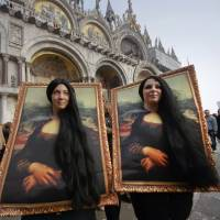 Two carnival revellers masquerade as Leonardo da Vinci's painting 'Mona Lisa' pose in St. Mark's Square in Venice, Italy, Sunday. Carnival-goers in Venice are being asked by police to momentarily lift their masks as part of new anti-terrorism measures for the annual festivities. | AP