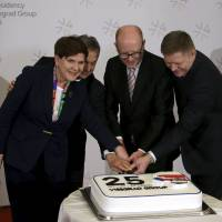 Visegrad Group (V4) member nations' prime ministers (from left) Poland's Beata Szydlo, Hungary's Viktor Orban, Czech Republic's Bohuslav Sobotka and Slovakia's Robert Fico cut a cake to celebrate the 25th anniversary of the establishment of the group during an extraordinary summit aimed at resolving the migration crisis, in Prague on Monday. | REUTERS