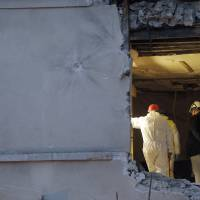 People work inside the damaged apartment in the Paris suburb of Saint-Denis Nov. 19. The woman who tipped police to the Islamic State commander of the Nov. 13 attacks in Paris says he told her he entered the Paris region among a multinational group of 90 extremists still scattered in the area. In an interview aired Thursday by RMC television and confirmed by her lawyer, the woman said Abdelhamid Abaaoud was proud of the attack that killed 130 people. | AP