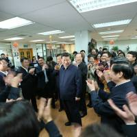 People applaud as Chinese President Xi Jinping (center) talks with editors in the general newsroom of the People's Daily in Beijing on Friday. | AP