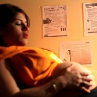 Noriany Rivera gets a checkup during her pregnancy in San Juan, Puerto Rico, on Wednesday. Notices on the wall explain how to prevent the Zika, dengue and chikungunya viruses. | REUTERS