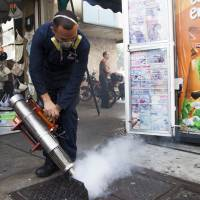 A worker from the Chacao municipality sprays insecticide into a sewer to eradicate mosquitoes that can cause the Zika virus in Caracas on Tuesday. | BLOOMBERG