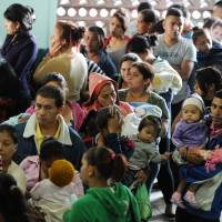 Fathers with their children crowd a hospital in Tegucigalpa on Monday. Honduran President Juan Orlando Hernandez on Friday declared the country on a preventive state of alert due to the Zika virus, which in the last 44 days killed a person and infected some 1,000. | AFP-JIJI